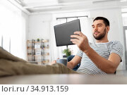 man with tablet pc resting feet on table at home. Стоковое фото, фотограф Syda Productions / Фотобанк Лори