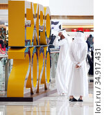 Dubai, United Arab Emirates, men in national costume are facing a promotional display for Expo 2020, the world exhibition to be held in Dubai in 2020 from October 20 (2019 год). Редакционное фото, агентство Caro Photoagency / Фотобанк Лори