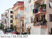 Residential houses with balconies are in the center of city. Red national flages hang on rails. Alanya is a beach resort city with own tourist industry. Turkey (2020 год). Редакционное фото, фотограф Кекяляйнен Андрей / Фотобанк Лори