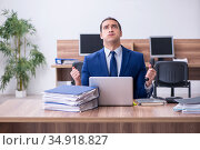 Young male employee unhappy with excessive work. Стоковое фото, фотограф Elnur / Фотобанк Лори