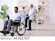 Young man in wheel-chair and old doctor radiologist. Стоковое фото, фотограф Elnur / Фотобанк Лори