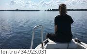 Teenage girl sitting on bow of riding motorboat, speedboat moving on lake water surface, copyspace. Стоковое видео, видеограф Кекяляйнен Андрей / Фотобанк Лори