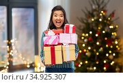 happy asian woman with christmas gifts at home. Стоковое фото, фотограф Syda Productions / Фотобанк Лори