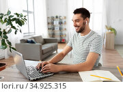 man with laptop and earphones at home office. Стоковое фото, фотограф Syda Productions / Фотобанк Лори