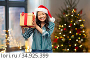 happy asian woman with christmas gift at home. Стоковое фото, фотограф Syda Productions / Фотобанк Лори