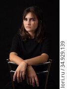 Портрет юной девушки сидящей на высоком стуле и сложившей руки на спинку стула. Стоковое фото, фотограф Иванов Алексей / Фотобанк Лори