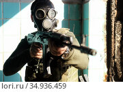military man in a gas mask is aiming to point his automatic weapon at the camera. Стоковое фото, фотограф Владимир Арсентьев / Фотобанк Лори