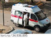 Врач заходит в автомобиль скорой помощи на вызове в период пандемии COVID-19 (2020 год). Редакционное фото, фотограф WalDeMarus / Фотобанк Лори