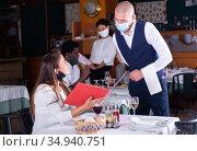 smiling waitress bringing order to female client in cafe during virus. Стоковое фото, фотограф Яков Филимонов / Фотобанк Лори