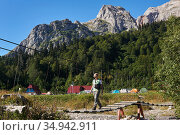 Woman hiker walks on a hinged bridge across the river against the background of a campground in a mountain valley. Стоковое фото, фотограф Евгений Харитонов / Фотобанк Лори