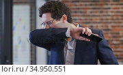 Man sneezing on his elbow at office. Стоковое видео, агентство Wavebreak Media / Фотобанк Лори