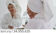 Woman in bathrobe applying face cream while looking in the mirror. Стоковое видео, агентство Wavebreak Media / Фотобанк Лори