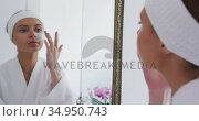 Woman in bathrobe applying face mask while looking in the mirror . Стоковое видео, агентство Wavebreak Media / Фотобанк Лори