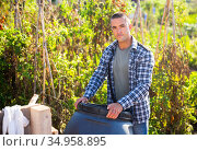 Farmer with a plastic barrel in summer garden. Стоковое фото, фотограф Яков Филимонов / Фотобанк Лори