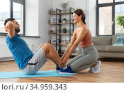man with personal trainer doing sit ups at home. Стоковое фото, фотограф Syda Productions / Фотобанк Лори