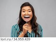 asian woman shows teeth through magnifying glass. Стоковое фото, фотограф Syda Productions / Фотобанк Лори