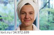 Portrait of a beautiful young woman with a towel turban on her head in front of the window. Стоковое видео, видеограф Алексей Кузнецов / Фотобанк Лори