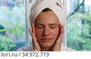 Young beautiful woman with a towel turban on her head massages her face with her hands in front of the window. Стоковое видео, видеограф Алексей Кузнецов / Фотобанк Лори