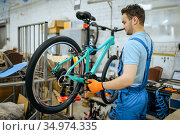 Bicycle factory, worker holds mountain bike. Стоковое фото, фотограф Tryapitsyn Sergiy / Фотобанк Лори