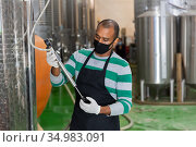 Winery worker checks the pressure in steel barrel. Стоковое фото, фотограф Яков Филимонов / Фотобанк Лори