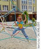 Маленькая  девочка карабкается по веревочной  пирамиде. Детская площадка. Стоковое фото, фотограф Ирина Борсученко / Фотобанк Лори