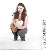 Curly hair woman holding teddy bear in hands, white background, studio shot. Стоковое фото, фотограф Кекяляйнен Андрей / Фотобанк Лори