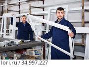 Two positive men professional labours with finished PVC profiles and windows. Стоковое фото, фотограф Яков Филимонов / Фотобанк Лори