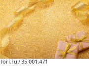 New Year's image for congratulations and inscriptions on golden glowing background, decorated with gifts and ribbon. Стоковое фото, фотограф Сергей Молодиков / Фотобанк Лори