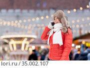 woman calling on smartphone over christmas market. Стоковое фото, фотограф Syda Productions / Фотобанк Лори