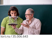 Old professor physicist and young student in the classroom. Стоковое фото, фотограф Elnur / Фотобанк Лори