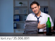 Alcohol addicted businessman working late in the office. Стоковое фото, фотограф Elnur / Фотобанк Лори