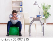 Employee exercising with swiss ball during lunch break. Стоковое фото, фотограф Elnur / Фотобанк Лори