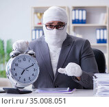 Bandaged businessman worker working in the office doing paperwor. Стоковое фото, фотограф Elnur / Фотобанк Лори