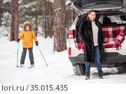 Mother waiting her daughter close to car until girl riding on ski in a forest, winter activities. Стоковое фото, фотограф Кекяляйнен Андрей / Фотобанк Лори