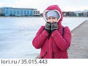 Adult woman wearing warm coat with hood on head and knit mittens standing on quay of frozen lake. Стоковое фото, фотограф Кекяляйнен Андрей / Фотобанк Лори