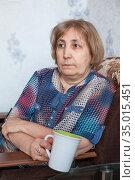 Caucasian mature woman holding tea cup, sitting in armchair in domestic room. Стоковое фото, фотограф Кекяляйнен Андрей / Фотобанк Лори