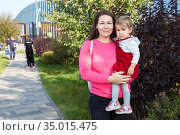 Caucasian mother holding little daughter in her arms, one year old toddler in red dress, outdoor, copy space. Стоковое фото, фотограф Кекяляйнен Андрей / Фотобанк Лори