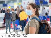 Caucasian woman wearing medical mask waiting her luggage in international airport area. Стоковое фото, фотограф Кекяляйнен Андрей / Фотобанк Лори