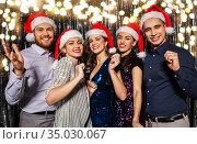 happy friends in santa hats at christmas party. Стоковое фото, фотограф Syda Productions / Фотобанк Лори