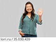 happy asian woman in glasses waving hand. Стоковое фото, фотограф Syda Productions / Фотобанк Лори