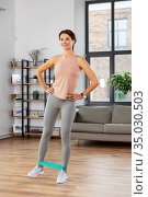 woman exercising with resistance band at home. Стоковое фото, фотограф Syda Productions / Фотобанк Лори