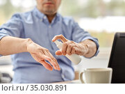 man using hand sanitizer at home office. Стоковое фото, фотограф Syda Productions / Фотобанк Лори