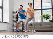 happy couple exercising and doing squats at home. Стоковое фото, фотограф Syda Productions / Фотобанк Лори
