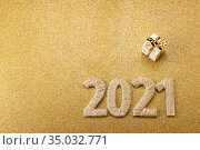 Happy new gold card with handcrafted lettering 2021 and gift. Space for text. Top view. Стоковое фото, фотограф Сергей Молодиков / Фотобанк Лори