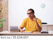 Young male student physics preparing for exams in the classroom. Стоковое фото, фотограф Elnur / Фотобанк Лори