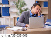 Young businessman employee unhappy with excessive work in the o. Стоковое фото, фотограф Elnur / Фотобанк Лори