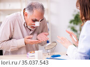 Old man visiting young female doctor for plastic surgery. Стоковое фото, фотограф Elnur / Фотобанк Лори
