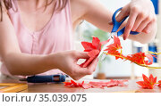 Woman decorating picture frame in scrapbooking concept. Стоковое фото, фотограф Elnur / Фотобанк Лори