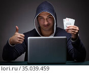 Young man wearing a hoodie sitting in front of a laptop computer. Стоковое фото, фотограф Elnur / Фотобанк Лори