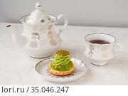 Shu cake with pistachio cream and a white tea set on the table. Стоковое фото, фотограф Катерина Белякина / Фотобанк Лори